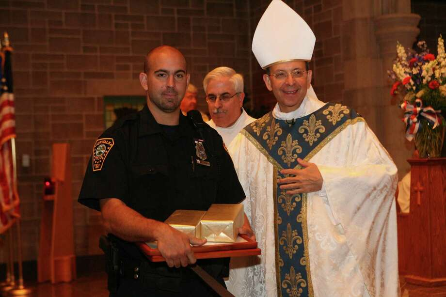 Norwalk police officer John Taranto receives an award from Bishop William Lori after mass at  Saint Catherine of Siena in Trumbull. The Diocese of Bridgeport  commemorated the ninth anniversary of 9/11 by honoring law enforcement, fire and emergency service personnel in a Blue Mass on Sunday, September, 12, 2010. Photo: B.K. Angeletti / ST / Connecticut Post