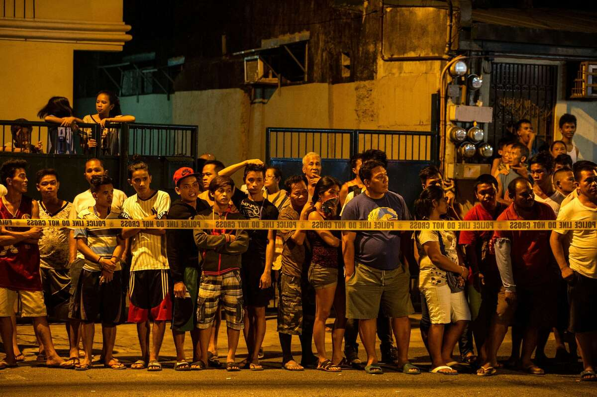 In this photo taken on July 19, 2016, shows residents behind a police line looking at the two dead bodies of an alleged drug dealer after a drug bust operation that turned into a gun fight in Manila. A United Nations human rights official has told AFP she expects to visit the Philippines to look into alleged extrajudicial killings, and sought guarantees for her as well as witnesses' safety. More than 1,500 people have died, police said, as the government launched crackdown on illegal drugs after Rodrigo Duterte won a landslide presidential election victory in May with a vow to kill tens of thousands of criminals.