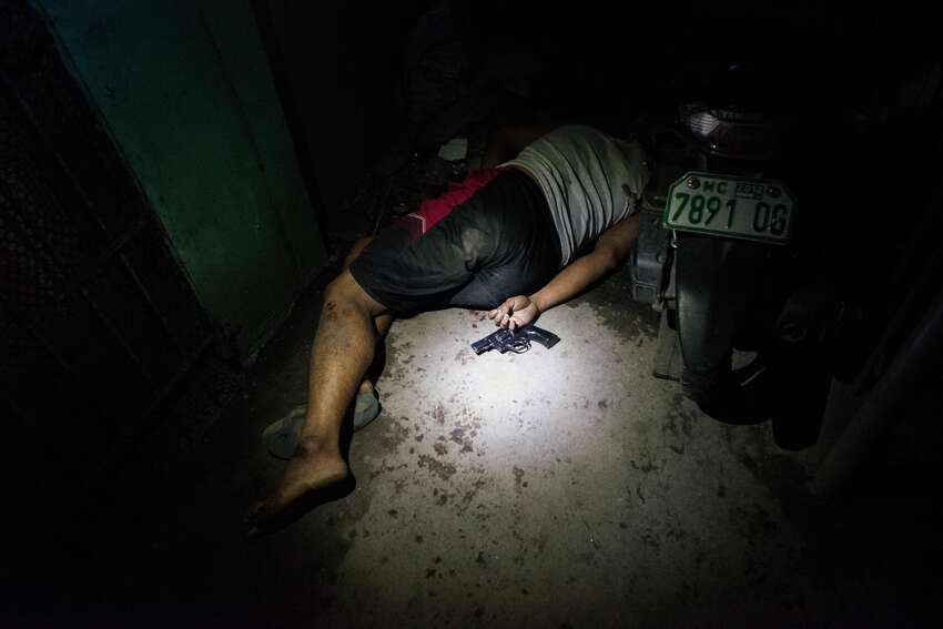 A drug suspect lies dead in a hallway during an alleged shootout with police on August 18, 2016 in Manila, Philippines. The death toll from the Philippines' war on drugs initiated by President Rodrigo Duterte has spiked to nearly 1,800 since he took office in June, a figure much higher than the 900 deaths previously cited by officials. International human rights advocates have condemned the killings as out of control and are calling on the government to end the nightly drug raids and investigate extrajudicial killings, although the president has lashed out at critics and threatened to withdraw from the United Nations. According to reports, investigations are still ongoing for 1,067 drug-related killings, reportedly carried out by vigilantes but it was unclear how many were directly related to the illegal drug trade.