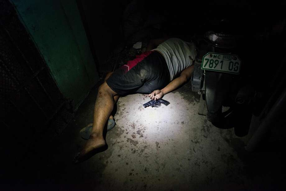 A drug suspect lies dead in a hallway during an alleged shootout with police on August 18, 2016 in Manila, Philippines. The death toll from the Philippines' war on drugs initiated by President Rodrigo Duterte has spiked to nearly 1,800 since he took office in June, a figure much higher than the 900 deaths previously cited by officials. International human rights advocates have condemned the killings as out of control and  are calling on the government to end the nightly drug raids and investigate extrajudicial killings, although the president has lashed out at critics and threatened to withdraw from the United Nations. According to reports, investigations are still ongoing for 1,067 drug-related killings, reportedly carried out by vigilantes but it was unclear how many were directly related to the illegal drug trade. Photo: Dondi Tawatao/Getty Images