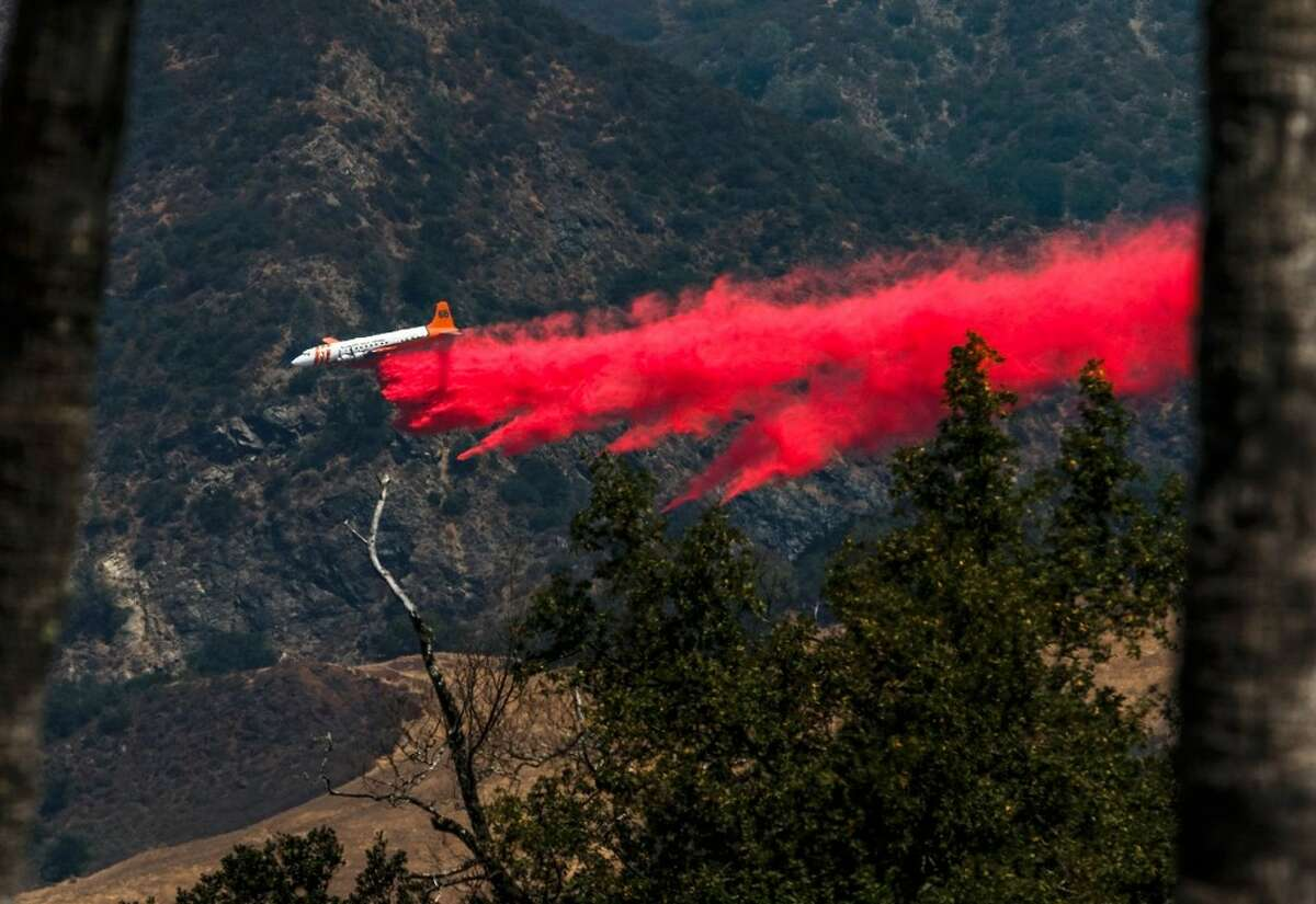 A plane aids in firefighting efforts behind Hearst Castle as a wildfire burns in San Simeon, Calif., Saturday, Aug. 20, 2016. A growing wildfire in central California has forced the closure of the historic Hearst Castle. Fire officials say the blaze was about 3 ½ miles from the hilltop estate on Saturday.