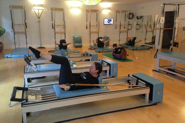 The Pilates hundred is a total body exercise stemming from the core that can be made easier performed on the floor or, as shown above, on a Pilates reformer. (Carin Lane / Times Union)