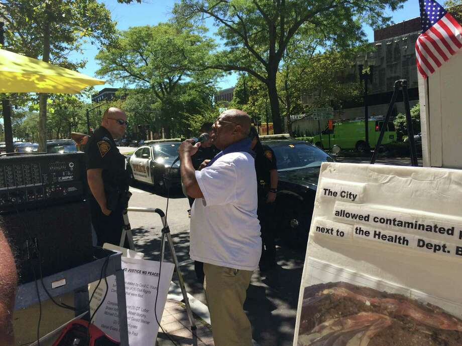 Community activist Cecil Young stages a protest in downtown Bridgeport over what he says are contimated dirt piles at the city health department. Photo: Frank Juliano