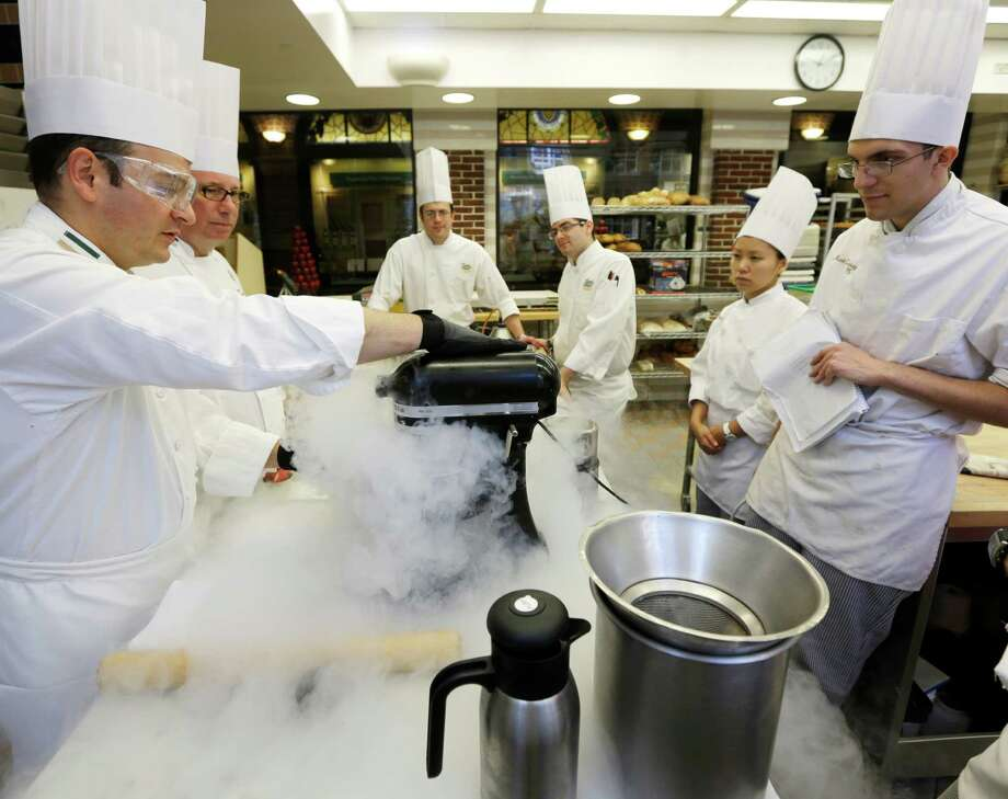 In this image taken on Friday, Sept. 14, 2012, Chef Francisco Migoya, left, demonstrates how to make strawberry sorbet by applying liquid nitrogen to a puree mixture at the Culinary Institute of America in Hyde Park, N.Y. This esteemed cooking school north of New York City is dramatically pumping up science instruction, saying that tomorrow's chefs will need more technical know-how in the age of molecular gastronomy and sous-vide. (AP Photo/Mike Groll) Photo: Mike Groll / AP