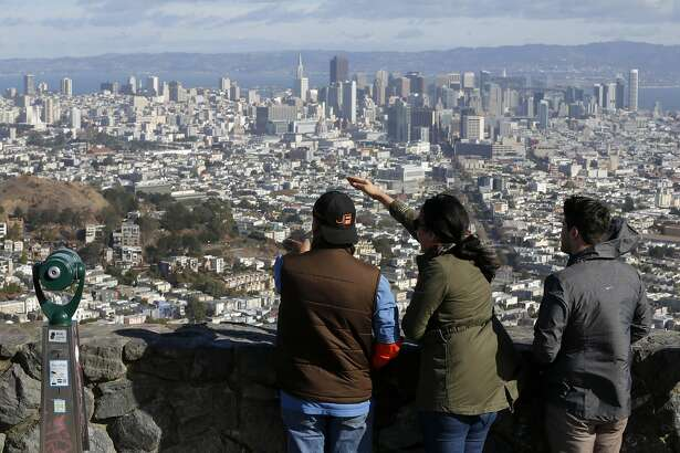 Tourists point out different parts of the city while enjoying a sunny but blustery day at Twin Peaks in San Francisco, California, on Sunday, Nov. 15, 2015.
