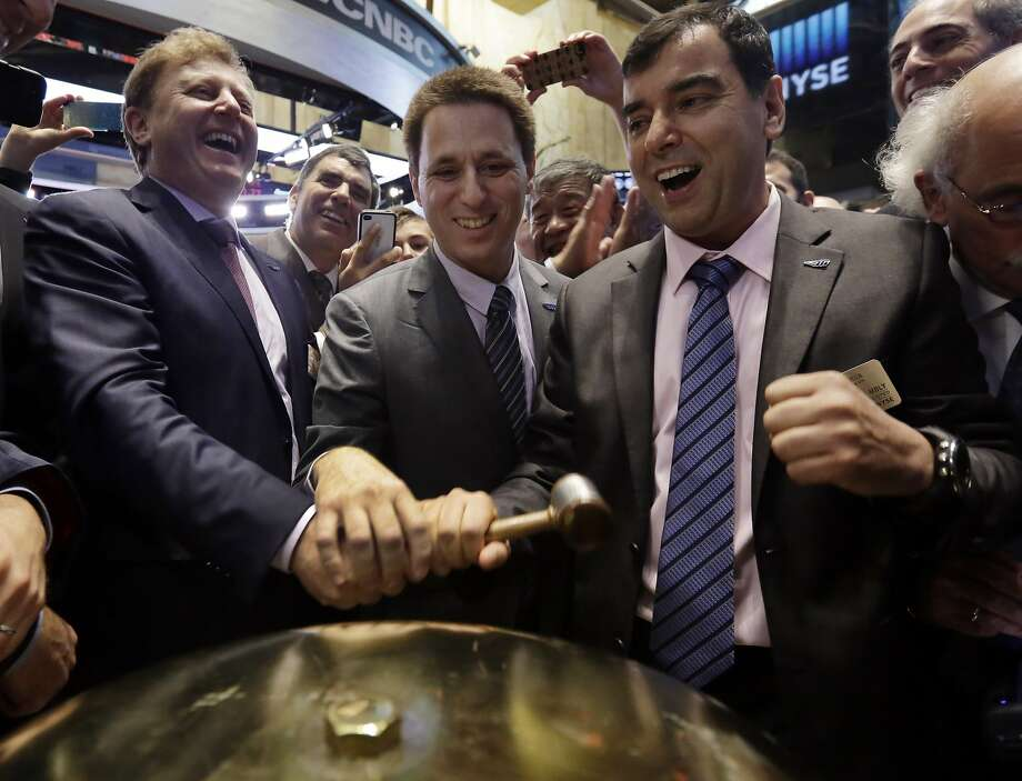 FILE - In a Aug. 1, 2014 file photo, Mobileye President & CEO Ziv Aviramon, left, CFO Ofer Maharshak, center, and Chairman Amnon Shashua, clasp hands to ring a ceremonial bell as their company's IPO begins trading, on the floor of the New York Stock Exchange.  Auto parts and electronics company Delphi Automotive is joining with Israeli software maker Mobileye to develop the building blocks for a fully autonomous car in about two years. The companies announced their partnership early Tuesday, Aug. 23, 2016. (AP Photo/Richard Drew, File) Photo: Richard Drew, Associated Press