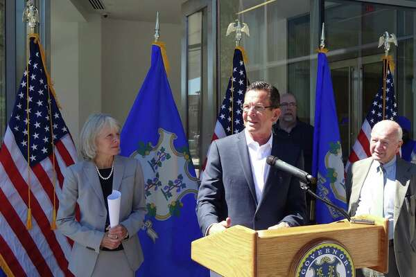 Gov. Dannel P. Malloy in New Haven, Conn. on August 23, 2016, where he detailed a study of his administration's First Five program that awards incentives to companies hiring at least 200 people in Connecticut. Malloy is flanked by Catherine Smith, commissioner of the Connecticut Department of Economic and Community Development; and state Sen. Joe Crisco.