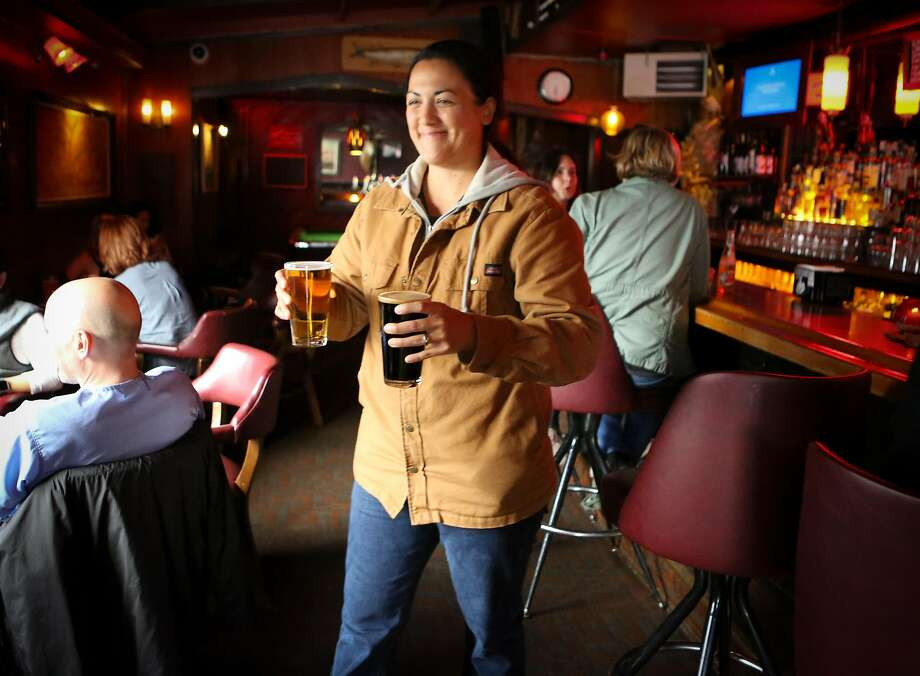 Kayla King carries a couple of pints back to her table at the Page bar on Divisadero in S.F. Photo: Amy Osborne, Special To The Chronicle