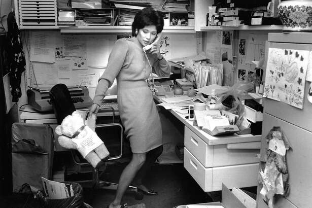 WENDY TOKUDA (July 31, 1990) The anchor works during a busy day at KPIX. According to the photo caption, she's returning calls, and the bear is from a young fan. Note the children's artwork on her filing cabinet.