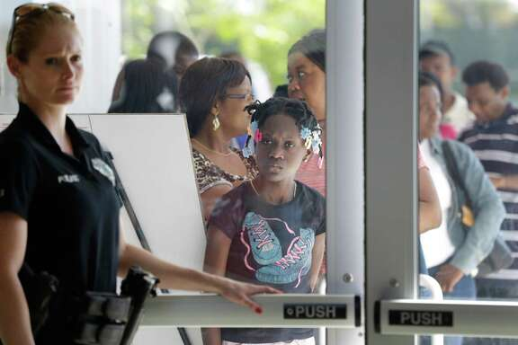 """A police officer holds the door as people line up outside the Joe Celestin Center in North Miami, Fla., during National Youth Enrollment Day, Saturday, Feb. 15, 2014. Dozens of organizations in Florida and around the country were participating in events to target so-called """"young invincibles,"""" uninsured young adults to inform them about their health insurance options under the Affordable Care Act. Insurers are counting on """"young invincibles"""" to offset the costs of covering older, sicker enrollees. (AP Photo/Wilfredo Lee)"""