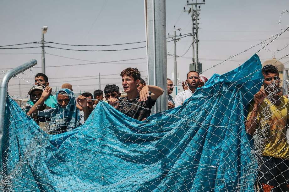 Men wait outside a fenced area at the Dibaga Camp for displaced people, in Hajj Ali, northern Iraq. Photo: Alice Martins, Associated Press