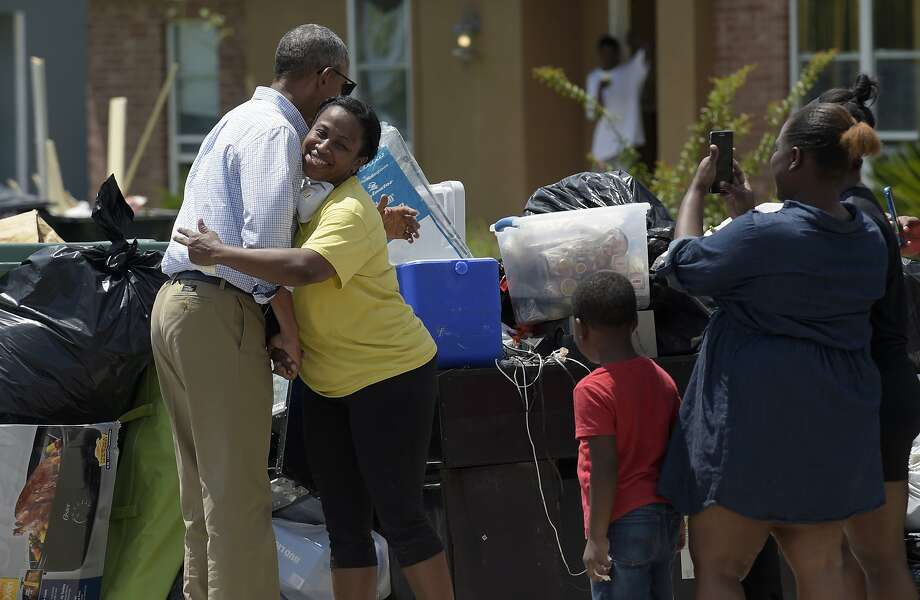 President Obama hugs Marlette Sanders as he tours Castle Place, a flood-damaged area of Baton Rouge, La. The president made his first visit to the flood-ravaged area. Photo: Susan Walsh, Associated Press