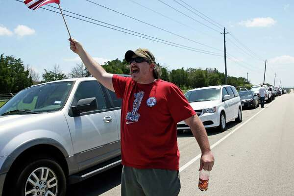Mike Bates waves the flag with Donald Trump supporters, arriving early in the day and waiting outside the gates of the Travis County Expo Center for the 7:30 p.m. rally of the Republican presidential candidate on August 23, 2016