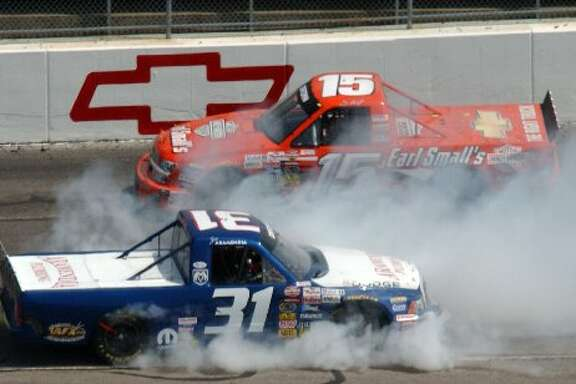 Joe Aramendia (31) spins out as Shane Hmiel (15) drives by during the NASCAR truck series Kroger 250 race at Martinsville Speedway in Martinsville, Va., April 17, 2004.