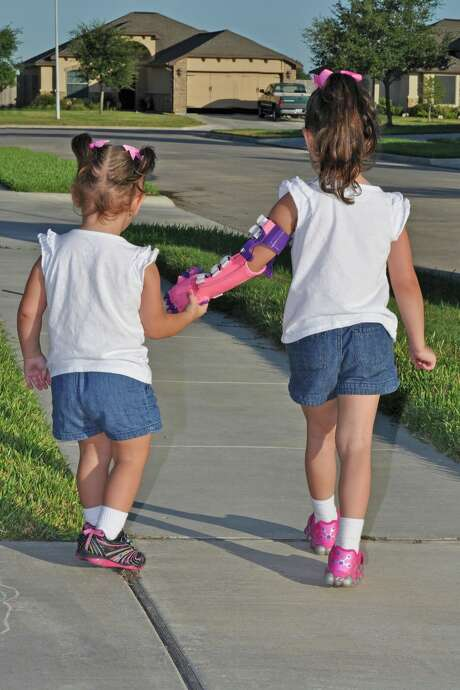 Katelyn Vincik, 5, of Victoria, received a prosthetic hand from the Clear Lake library, which used its 3D printer to make it.  She is seen here walking with her sister Lacey. 3. Photo: Family Photos / Family photos
