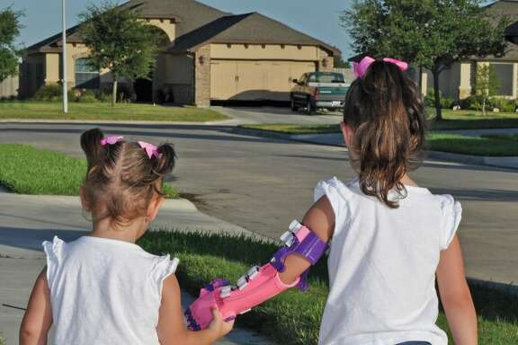 Katelyn Vincik, 5, of Victoria, received a prosthetic hand from the Clear Lake library on July 30th, 2016, which used it's 3D printer to make it.  She asked for her new hand to be pink and purple.   She is seen here walking with her sister Lacey. 3.