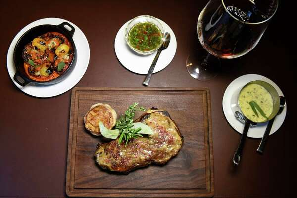 Prime Bone-In Strip with a side of Blackened Tomatoes, Lime Chimichurri sauce and Bearnaise sauce on Friday, Aug. 19, 2016, at Salt & Char in Saratoga Springs, N.Y. (Cindy Schultz / Times Union)