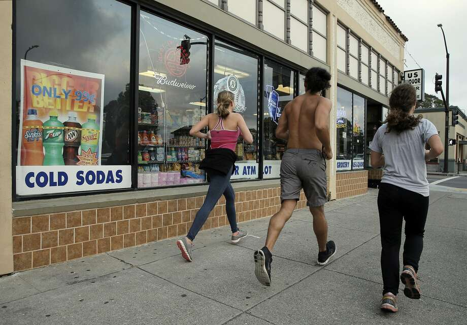 Joggers run by a sign advertising sodas for 99 cents at US Liquor Beer and Wine store in Berkeley on Monday, August 22, 2016. Photo: Carlos Avila Gonzalez, The Chronicle