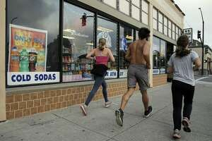 Joggers run by a sign advertising sodas for 99 cents at US Liquor Beer and Wine store in Berkeley, Calif., on Monday, August 22, 2016. A new UC-Berkeley study shows that Berkeley's first-of-its-kind-in-the-nation tax on sodas and other sugary drinks has led to a drop in soda consumption in the city's most low-income neighborhoods.