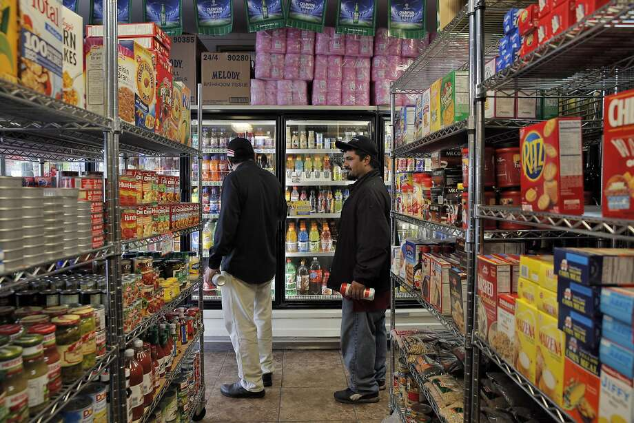 Elias Serrano (left) and Francisco Morales shop for soda at US Liquor Beer & Wine in Berkeley, where sugary drinks are subject to a tax of a penny an ounce. Photo: Carlos Avila Gonzalez, The Chronicle