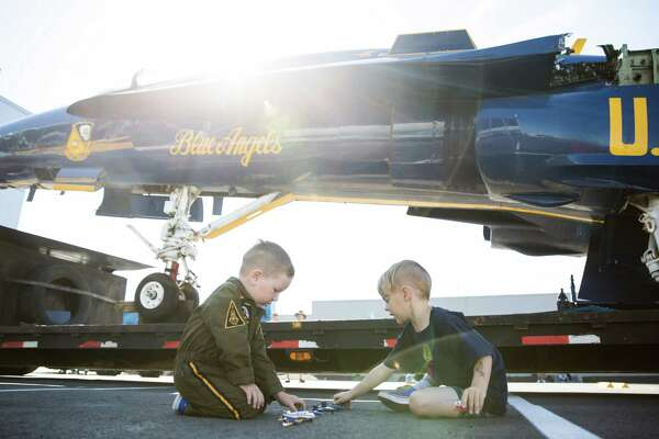 Caderyn Jenkins, 3, and Cameron Nichols-Rage, 5, meet and team their toy flight teams up under the Museum of Flight's new Blue Angel F/A-18C Hornet as it awaits assembly on Tuesday, Aug. 23, 2016.
