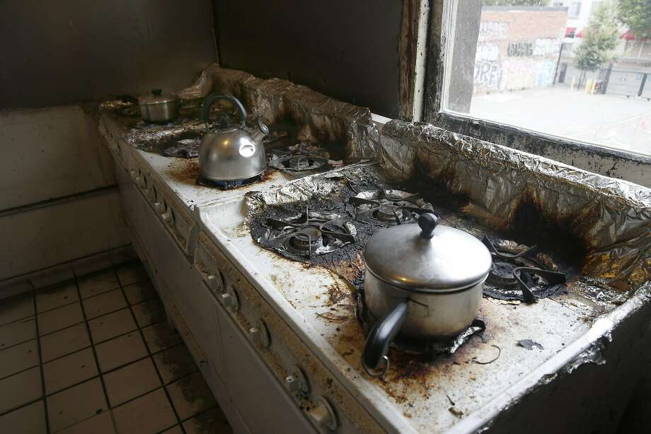 Tenants cook breakfast in the communal kitchen of a residential hotel. The Oakland city attorney's suit says owners have ruined living conditions. Photo: Paul Chinn, The Chronicle