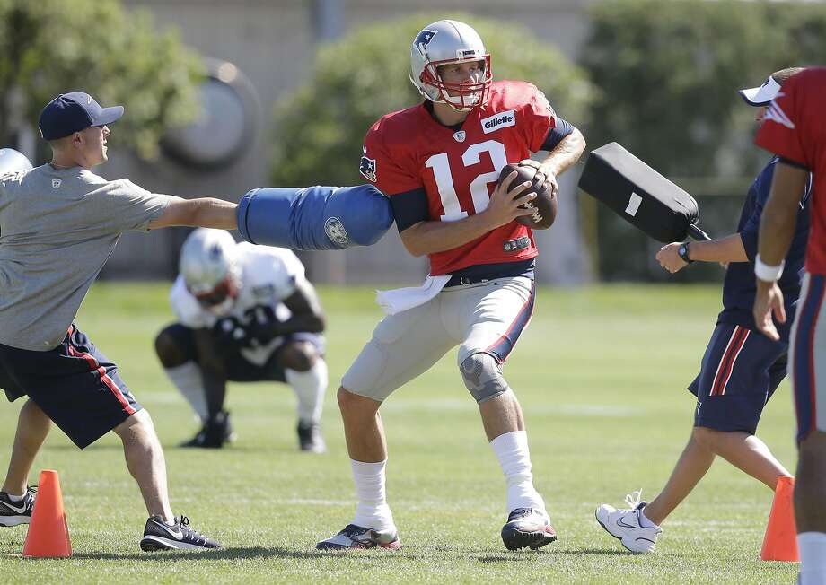 Tom Brady drops back to pass during Tuesday's practice. He said an accident with scissors will not keep him from being able to play against defending NFC champion Carolina on Friday. Photo: Steven Senne, Associated Press