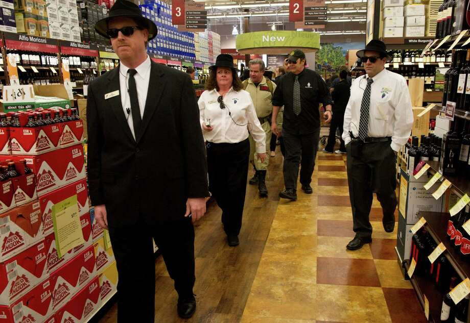 Dan Aykroyd is escorted to a table by employees dressed as Blues Brothers during a bottle signing event at Total Wine & More in Norwalk on Saturday, April 6, 2013. Photo: Lindsay Perry / Lindsay Perry / Stamford Advocate