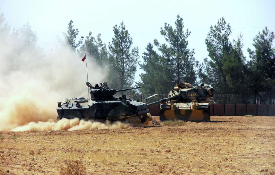 A Turkish army tank and an armored vehicle are stationed near the border with Syria on Tuesday. Turkish artillery pummeled Islamic State-controlled Jarablus, Syria, for a second day as reports circulated that Turkish-backed Syrian rebels were preparing to storm the town. Photo: SUB / IHA