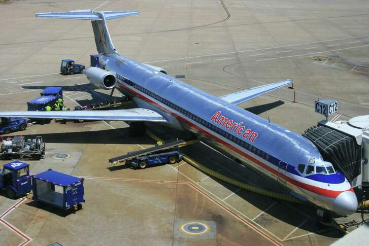 Workers prepare an American Airlines MD-80 for departure at Dallas-Fort Worth International Airport this spring. American is phasing out its MD-80s and replacing them with the Airbus A321 and the Boeing 737-800, which offer 35 percent better fuel efficiency.