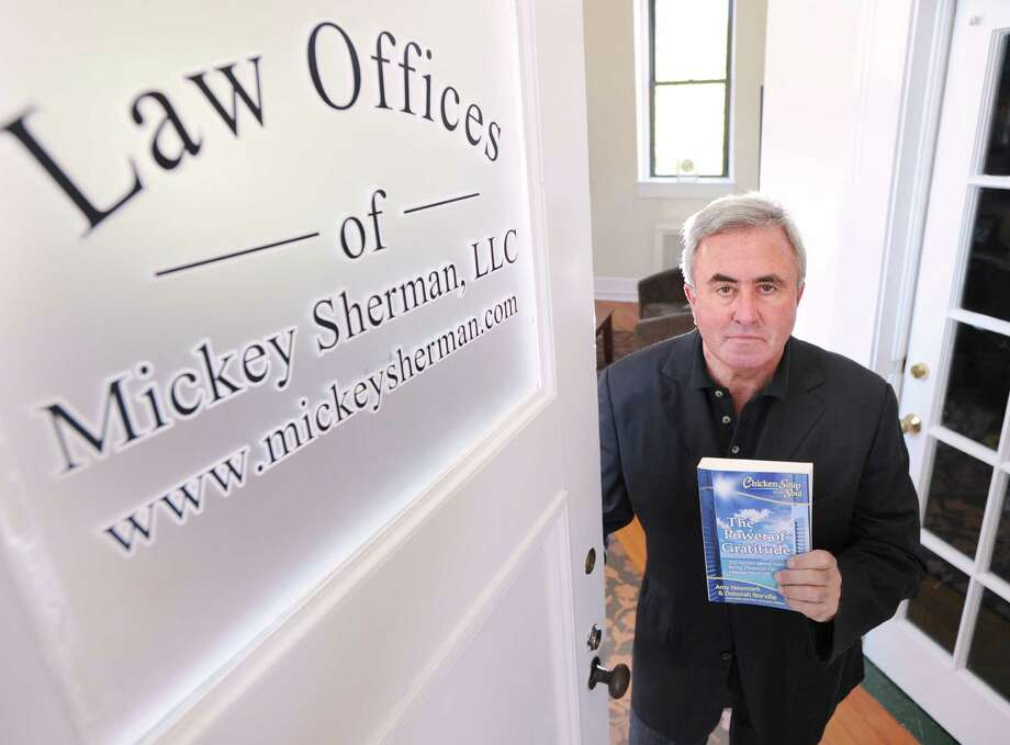 """Attorney Mickey Sherman holds the book """"Chicken Soup for the Soul: The Power of Gratitude,"""" in his Greenwich office. Photo: Bob Luckey Jr. / Hearst Connecticut Media / Greenwich Time"""