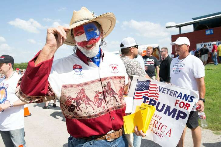 Marco Spence, his face painted in the US colors, poses with a poster to attend the campaign rally held by Republican presidentialcandidateDonald Trump in Austin, Texas, Aug. 23, 2016.