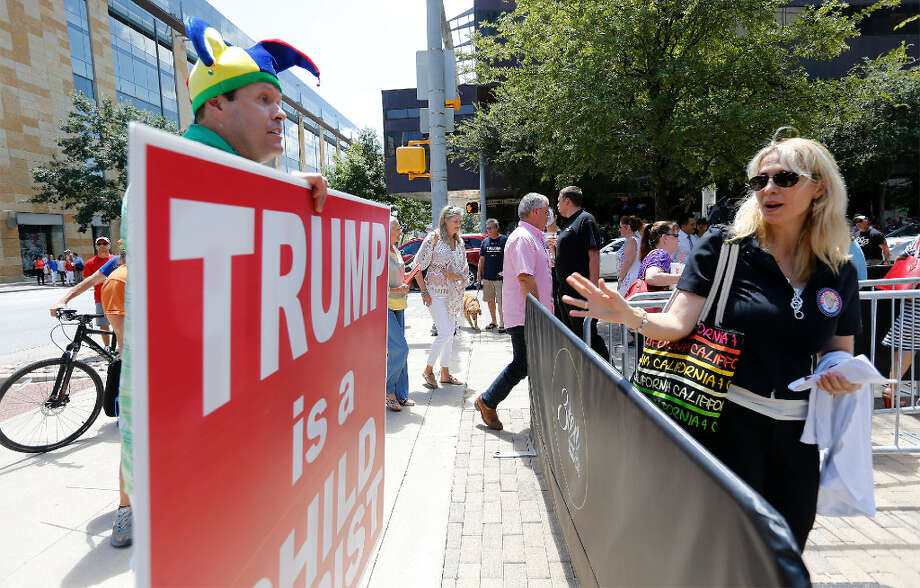 Robert Morrow, Chairman of the Travis County Republican Party (left) exchanges words with a woman entering the Moody Theater for a taping of a town hall with Republican Presidential candidate Donald Trump and Fox News in Austin on Tuesday, Aug. 23, 2016. 
