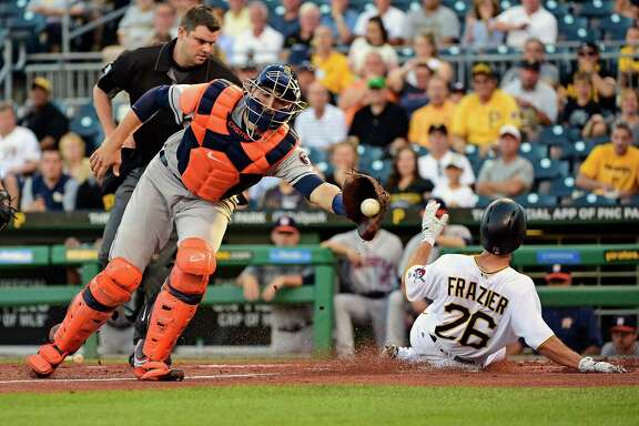 Adam Frazier beats the throw to Astros catcher Jason Castro to score the first of the Pirates' four runs in the first inning Tuesday night.