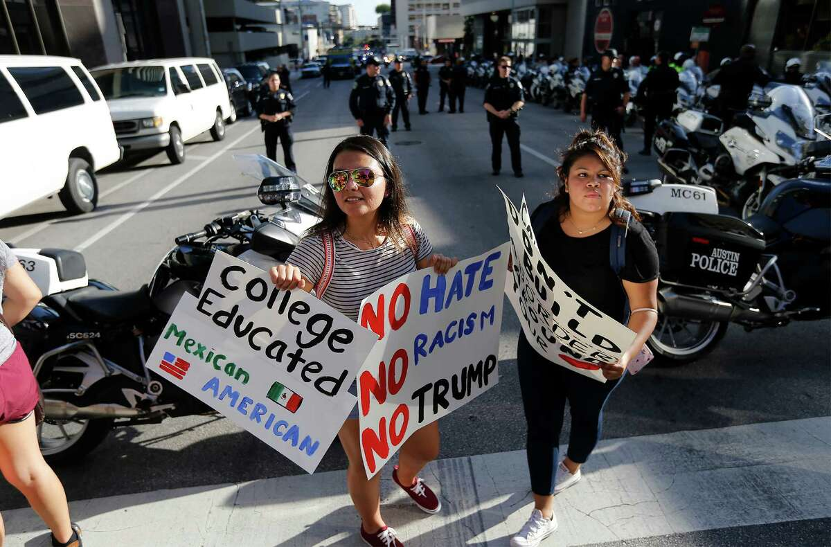 Sylvia Servin (left) and Jamileth Ortega join other demonstrators at a street corner near Lavaca and 6th Streets awaiting Republican presidential candidate Donald Trump to appear for his fundraising event in Austin on Tuesday, Aug. 23, 2016. Demonstrators from the Texas Democratic Party along with other individuals gathered to oppose Trump's presence in Austin and to advocate for Hillary Clinton in the upcoming presidential election. Along with the fundraiser, Trump made an appearance at a town hall meeting and rally in the Austin area. (Kin Man Hui/San Antonio Express-News)