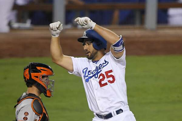 Los Angeles Dodgers' Rob Segedin celebrates after scoring on a solo home run, as San Francisco Giants catcher Buster Posey kneels at the plate during the second inning of a baseball game, Tuesday, Aug. 23, 2016, in Los Angeles. (AP Photo/Mark J. Terrill)