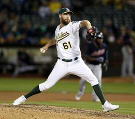 Oakland Athletics' John Axford pitches in 8th inning against Cleveland Indians during MLB game at Oakland Coliseum in Oakland, Calif., on Tuesday, August 23, 2016.
