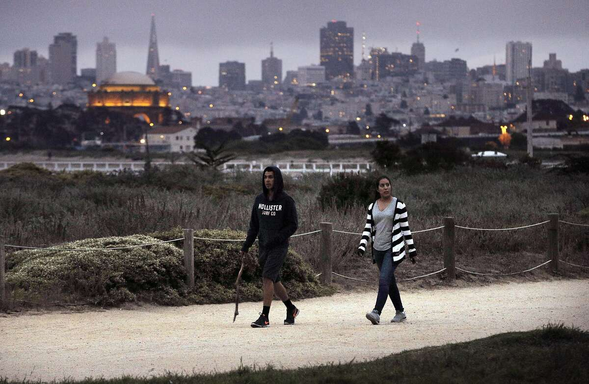 Fernando Ruiz and Nayeli Cazabal, right, walk along the path at Chrissy Field in San Francisco, Calif., on Tuesday, August 23, 2016.