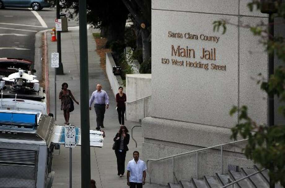 Pedestrians walk past the Santa Clara County Jail in San Jose, Calif. where a San Jose Police officer was booked Tuesday after being arrested on suspicion of five felonies during a citywide gang takedown. Photo: Karl Mondon (/San Jose Mercury News Via AP) / /