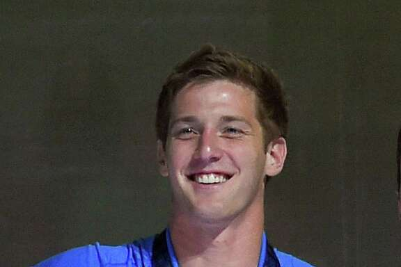 "In this July 3, 2016, file photo, U.S. swimmer Jimmy Feigen smiles during the men's 400-meter relay team medal ceremony at the U.S. Olympic swimming trials, in Omaha, Neb. Feigen apologized for the ""serious distraction"" he and three teammates caused at a gas station during the Rio Olympics, saying he omitted facts in his statement to police. Feigen says in a statement posted Tuesday, Aug. 23, 2016, on the website of his lawyer in Austin that ""I omitted the facts that we urinated behind the building and that Ryan Lochte pulled a poster off the wall."""