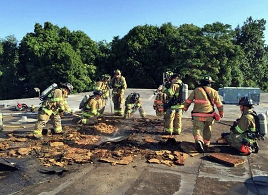 """Milford firefighters on the roof of a fire at Drillmasters-El Dorado Tool at 326 Boston Post Road on Wednesday, Aug. 24, 2016. When employees arrived for work on Wednesday morning, they found that smell had gotten stronger overnight. One worker then went on the roof and found a hot spot. """"The worker cut a hole in the roof and the flames came out,"""" Hall said. """"Thank God this didn't happen on a weekend.'' Photo: Anthony Fabrizi /Milford Fire Department"""