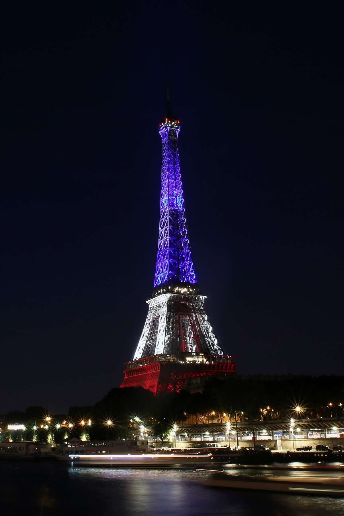 The Eiffel Tower is illuminated in the French national colors in honor of the victims of Thursday's attack in Nice, south of France, in Paris Friday, July 15, 2016. As new details emerged Friday about the Tunisian man who drove a truck through crowds celebrating Bastille Day in Nice, killing at least 80 people and wounding hundreds others, French leaders extended a state of emergency imposed after the Nov. 13 Paris attacks and vowed to deploy thousands of police reservists on the streets. (AP Photo/Thibault Camus)