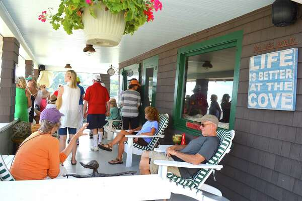 """""""Life is better at the cove,"""" and visitors appear to agree while they take a rest at Robin Tauck's historic waterside house Sunday, August 21, 2016, during the Westport Historical Society's tour of Old Mill Pond in Westport, Conn."""