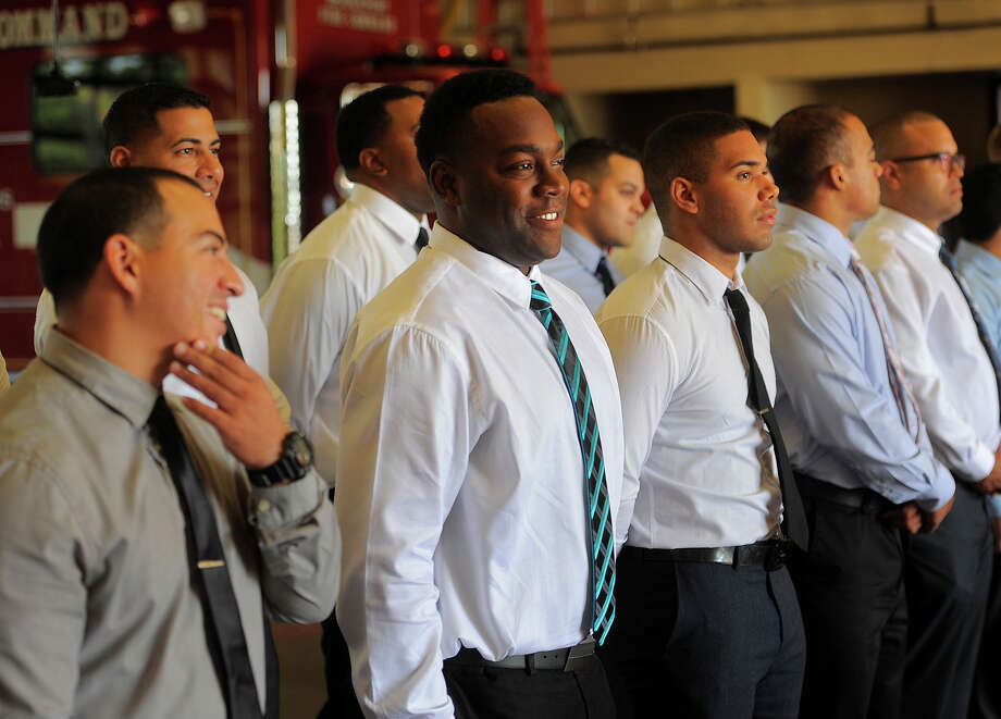 From left; New firefighter trainees Christopher Sanchez and Wesley Shirley, both of Bridgeport, smile as they wait to be introduced with their class of 23 new recruits at Bridgeport Fire Department Headquarters in Bridgeport, Conn. on Wednesday, August 24, 2016. Photo: Brian A. Pounds / Hearst Connecticut Media / Connecticut Post