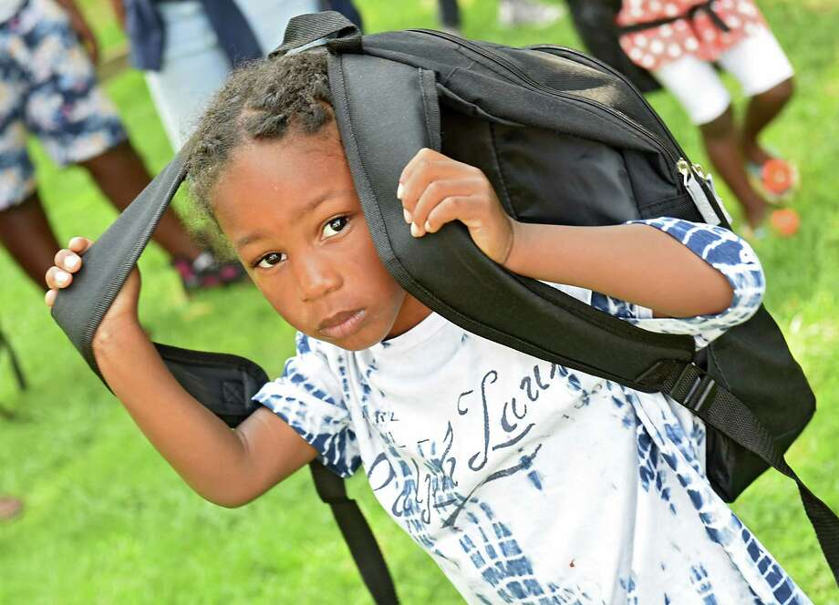 Nyshaun Miller, 4, of Albany puts on a brand new backpack during a backpack giveaway at Sheridan Park on Wednesday, Aug. 24, 2016 in Albany, N.Y. Members of Interfaith Partnership for the Homeless gave the backpacks away to children and parents as part of their summer youth program. (Lori Van Buren / Times Union) Photo: Lori Van Buren