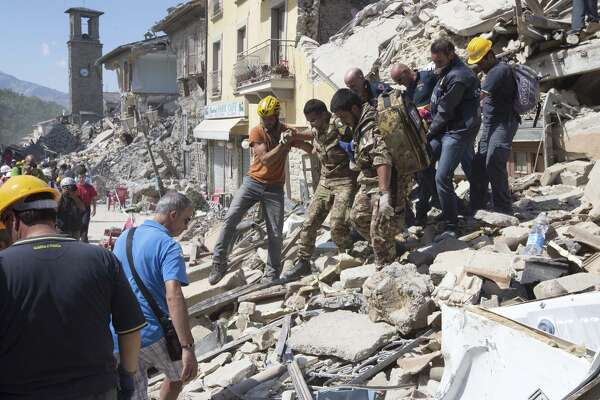 Rescuers carry a person from the rubble after a strong earthquake hit Amatrice on August 24, 2016.  Italy was struck by a powerful, 6.2-magnitude earthquake in the night, which has killed at least 63 people and devastated dozens of houses  in the Lazio village of Amatrice. (Photo by Riccardo De Luca/Anadolu Agency/Getty Images)