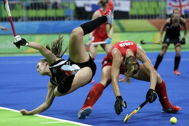 New Zealand's Rose Keddell, left, falls as she fights for the ball with Britain's Crista Cullen, right, during a women's field hockey semifinal match at 2016 Summer Olympics in Rio de Janeiro, Brazil, Wednesday, Aug. 17, 2016. (AP Photo/Hussein Malla)