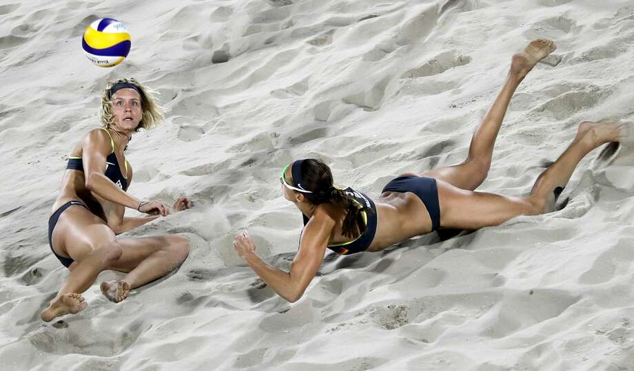 Germany's Kira Walkenhorst, right, and Laura Ludwig dive for the ball during the women's beach volleyball gold medal match against Brazil's Barbara Seixas de Freitas and Agatha Bednarczuk at the 2016 Summer Olympics in Rio de Janeiro, Brazil, Thursday, Aug. 18, 2016. (AP Photo/David Goldman) Photo: David Goldman/AP