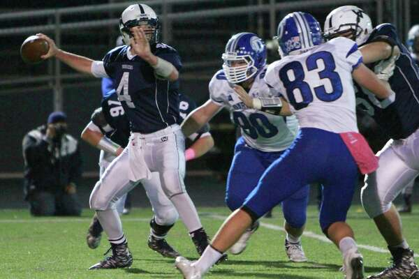Wilton's R.J. Romeo drops back to pass under pressure from Darien's Mark Evanchick (90) and Quinn Fay (83) during a varsity football game on Oct. 30, 2015 in Wilton.