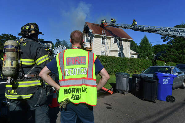 Norwalk firefighters battle a blaze that erupted on the third floor of a residential home at 2 Platt S. in Norwalk, Tuesday, Aug. 23.
